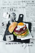 A burger with beef, a fried egg, pickled beetroot, and pineapple slices