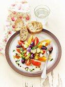 Lacto-fermentierte Tomaten, Gurken und Oliven mit Kräutern und Knoblauchbrot