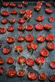 Roasted tomatoes on a black baking sheet