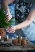 Frau schneidet Minze zum dekorieren von Mousse au Chocolate