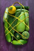 Various courgettes wrapped in netting with a handle