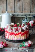 A strawberry and mascarpone torte decorated with white chocolate and macarons