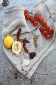 Lemons, tomatoes, chillies, and spices on a linen cloth