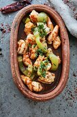 Chilli prawns with herbs in a rustic serving dish (top view)