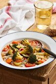 Minestrone in an enamel plate on a rustic wooden table