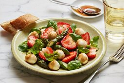 A salad with green asparagus, strawberries, mini mozzarella balls and fresh basil