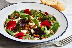 Green salad with sheep's cheese, baked chickpeas and edible petals