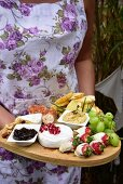 A woman holding a cheese plate with fruit, houmous, and bruschetta