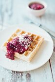 A Belgian waffle with plum compote and coconut chips