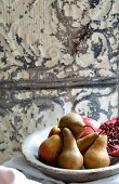 Pears and pomegranates in a stone bowl