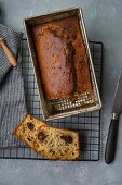 Banana bread with chocolate pieces in a baking tin on a cooling rack (top view)