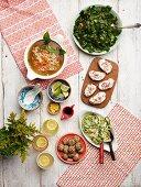 Ramen soup, kale, sour cream and radish spread, courgette salad, grain balls, and herb lemonade
