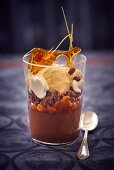 A chocolate and caramel dessert with vanilla ice cream in a glass