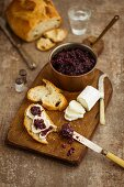 Copper pan filled with red onion chutney on a dark wooden chopping board with crusty bread vintage cutlery and sliced goat s cheese topped with chutney
