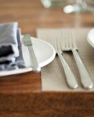 A place setting with cutlery and napkins on a wooden table (close up)
