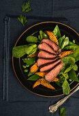 Steakscheiben mit Süsskartoffel-Pommes auf Salat
