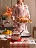 A woman serving a roast goose (Christmas)