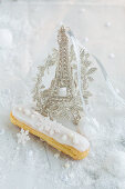 An eclair and a silver Eiffel Tower model for Christmas