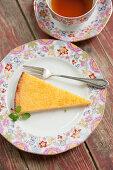 A slice of lemon tart served with tea