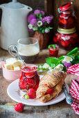 Croissant mit Erdbeerkonfitüre, Butter und Kaffee