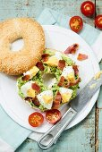 A bagel with bacon, avocado and egg