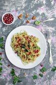 Spaghetti with parsley and walnut pesto, eggplant, and pomegranate