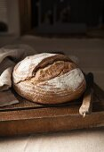 A loaf of sourdough bread on a chopping board with bread knife and linen cloth