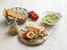 Crispbreads with avocado and cottage cheese, boiled eggs, tomatoes and sprouts