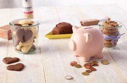 Biscuits and a piggy bank with some coins on a wooden table
