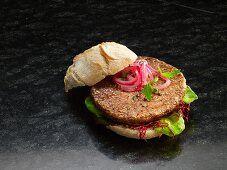 A hamburger with red onions and lettuce