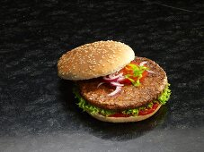 A hamburger in a sesame seed bun with onions, tomato, lettuce and ketchup