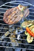 Steak and zucchini on a grill with herbs and spices