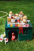 Chocolate cupcakes in teacups on a pet house for a children's party in the garden