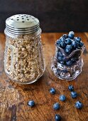 Granola in an antique jar and wild blueberries in a glass jar