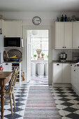 Dining area and chequered floor in white kitchen