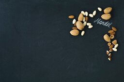 Almonds, whole and hulled, arranged around the German word for almond written in chalk on a blackboard