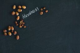 Hazelnuts, whole and hulled, arranged around the German word for hazelnut written in chalk on a blackboard
