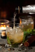 Pouring Prosecco into a Bourbon and Mint Cocktail