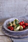 Ground elder quenelles with braised tomatoes