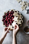 A cherry pie being topped with shortcrust pastry stars