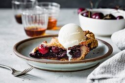 A slice of gluten-free cherry pie with vanilla ice cream on a plate