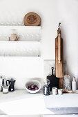 Kitchen utensils on worksurface below shelves of glasses