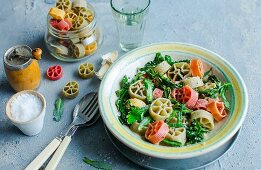Colourful wheel-shaped pasta with broccoli leaves and garlic