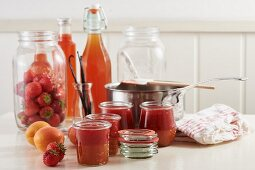 Strawberry and apricot jam in glass jars, with fresh apricots and strawberries