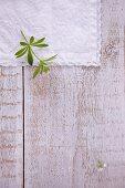 A woodruff leaf on a white linen cloth