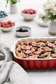 A goat's cheese and berry bread pudding in an ovenproof dish on a table