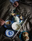 Coffee, muesli, a cheese dip and chocolate crispbread on a breakfast tray