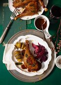 Goose leg in a baked plum and spiced sauce with red cabbage and hasselback potatoes