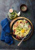 Spaghetti carbonara with ham and egg yolk