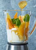 Ingredients for orange and mango dessert with honey in a mixer